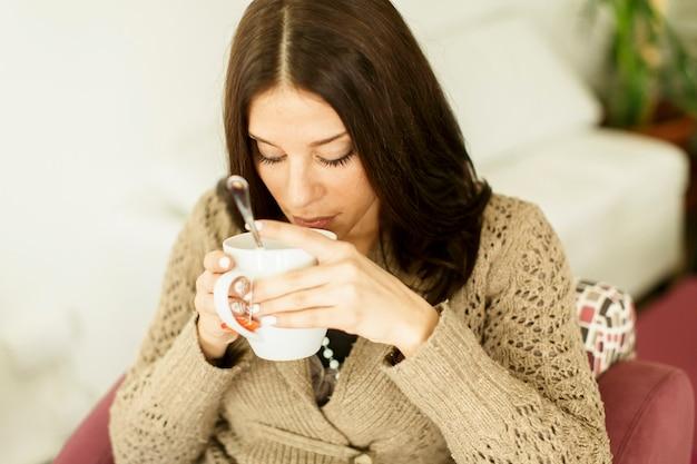 Młoda kobieta pije herbatę
