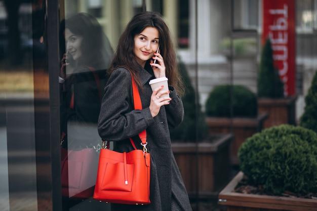Młoda kobieta pije kawę i używa telefon w miasteczku