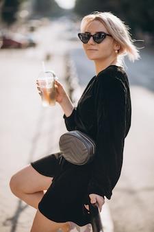 Młoda kobieta pije kawę iść na zewnątrz ulicy