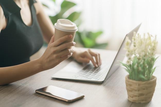 Młoda kobieta pije kawę od rozporządzalnej filiżanki i używa komputerowego laptop na pracy biurku.