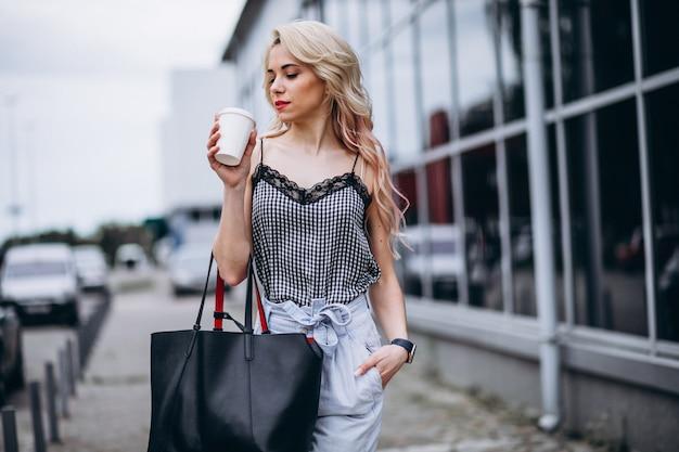Młoda kobieta pije kawę poza ulicą