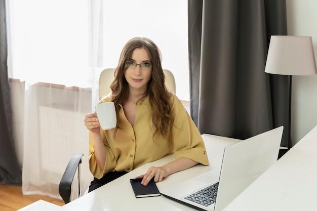 Młoda kobieta pije kawę przy biurkiem