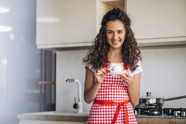 Młoda kobieta pije kawę przy kuchnią w ranku