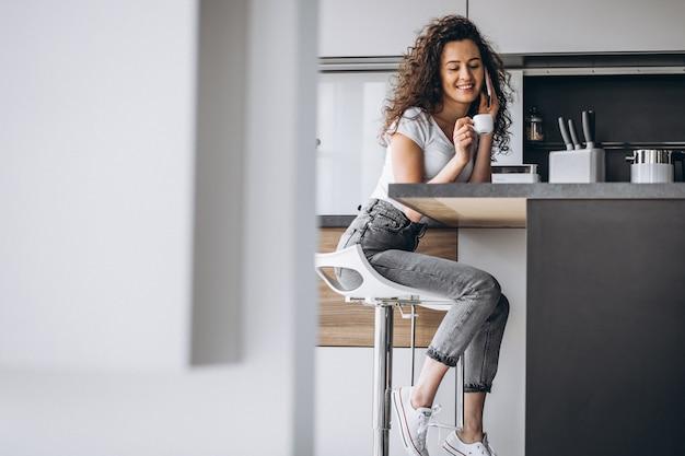 Młoda kobieta pije kawę przy kuchnią