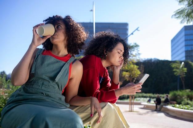 Młoda kobieta pije kawę, siedząc na ławce na ulicy, podczas gdy jej przyjaciółka rozmawia przez telefon