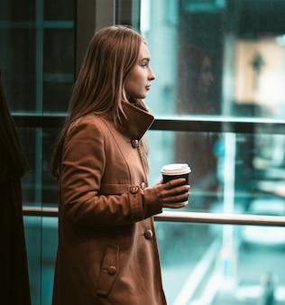 Młoda kobieta pije kawę w centrum biznesowym