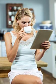 Młoda kobieta pije kawę w domu
