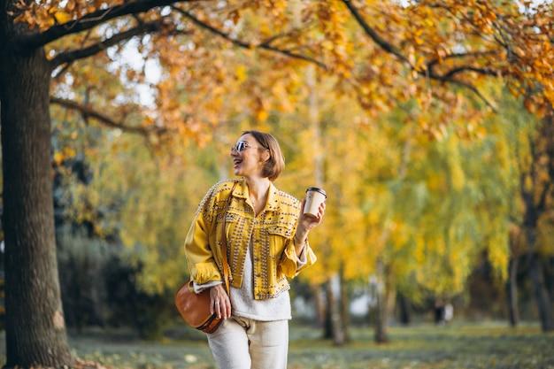 Młoda kobieta pije kawę w jesień parku