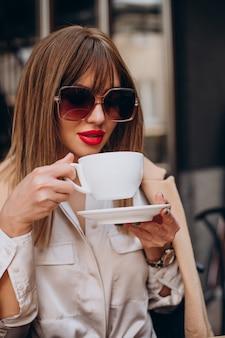 Młoda kobieta pije kawę w kawiarni na tarasie