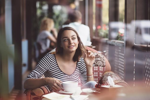 Młoda kobieta pije kawę w miastowej kawiarni