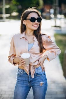 Młoda kobieta pije kawę w parku