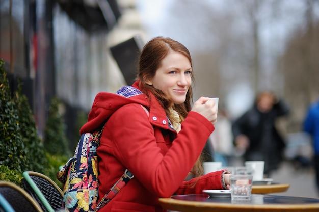 Młoda kobieta pije kawę w paryskiej kawiarni ulicy
