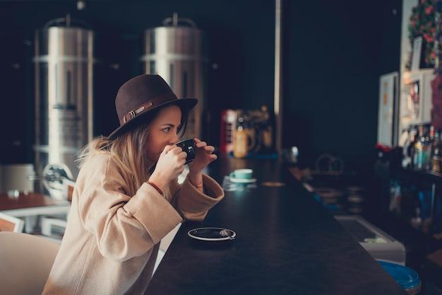 Młoda kobieta pije kawę w sklep z kawą w brown pulowerze i brown kapeluszu
