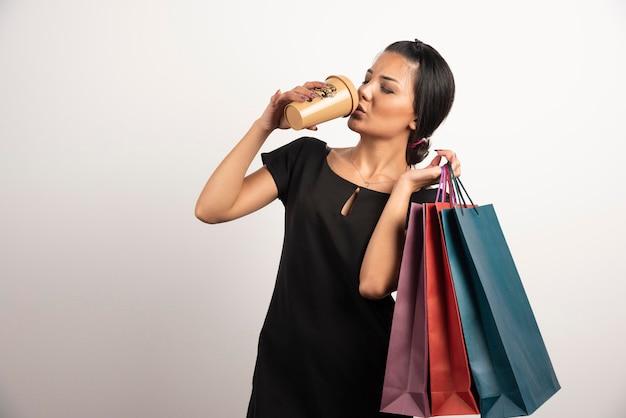 Młoda kobieta pije kawę z torbami na zakupy.