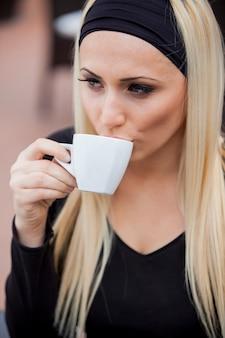 Młoda kobieta pije kawę