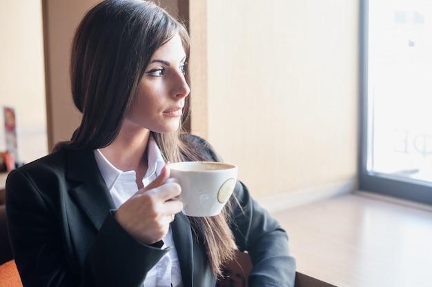 Młoda kobieta pije kawowy przyglądającego okno