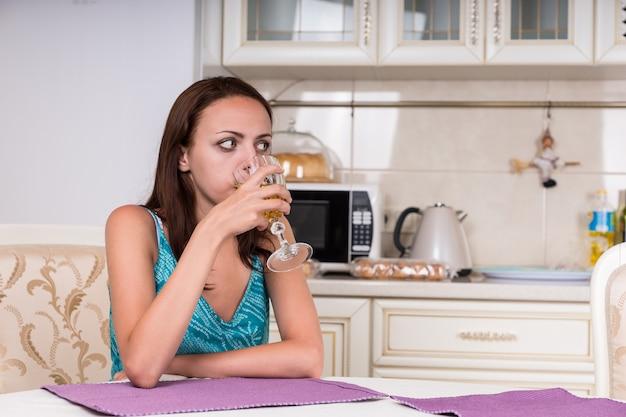 Młoda kobieta pije kieliszek wina, siedząc przy stole w kuchni i patrząc na odległość.