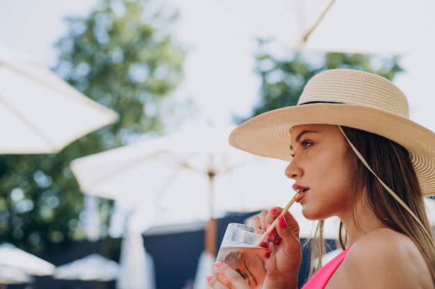 Młoda kobieta pije koktajl i leży na leżaku