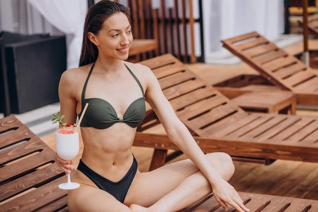 Młoda kobieta pije koktajl przy basenie