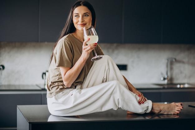 Młoda kobieta pije lemoniadę ze szkła w kuchni