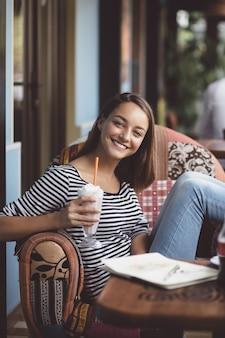 Młoda kobieta pije milkshake