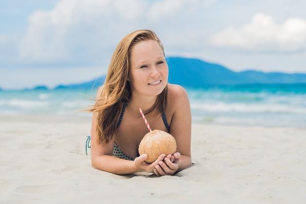 Młoda kobieta pije mleko kokosowe na plaży