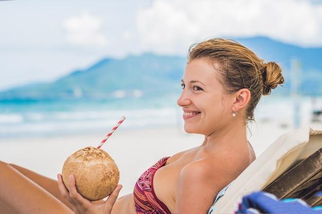 Młoda kobieta pije mleko kokosowe na szezlong na plaży