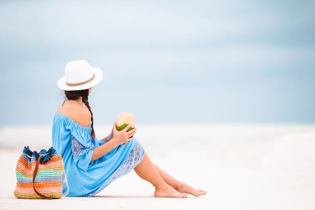 Młoda kobieta pije mleko kokosowe podczas tropikalnych wakacji