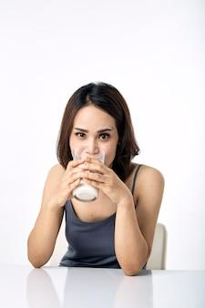 Młoda kobieta pije mleko na stole