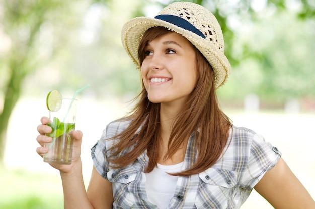 Młoda kobieta pije mojito
