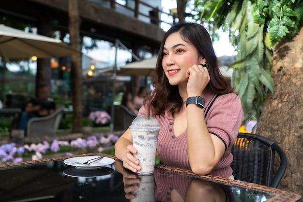 Młoda kobieta pije mrożone mleko frappe w kawiarni