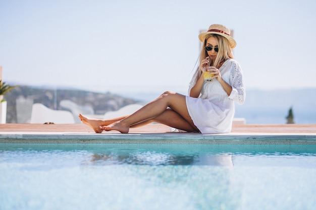 Młoda kobieta pije sok bu basen