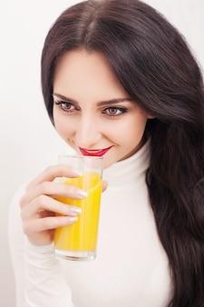 Młoda kobieta pije świeży sok pomarańczowy