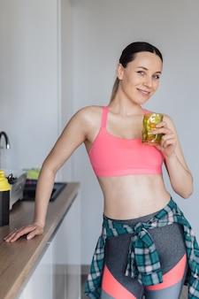 Młoda kobieta pije szklankę wody po treningu