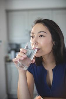 Młoda kobieta pije szkło woda w kuchni