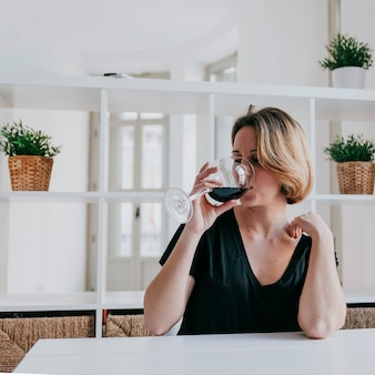 Młoda kobieta pije wino