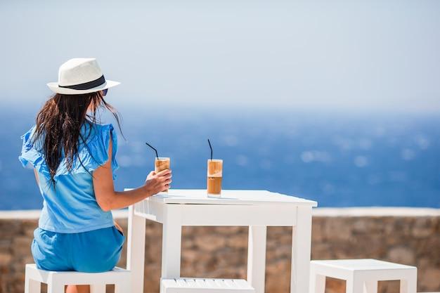 Młoda kobieta pije zimną kawę cieszy się dennego widok. piękna kobieta relaksuje podczas egzotycznego wakacje na plaży cieszy się frappe