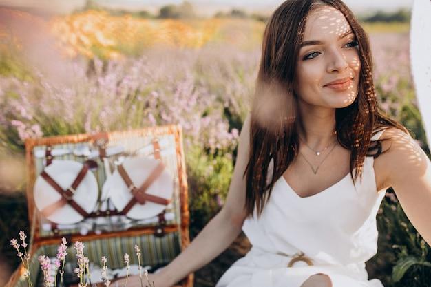Młoda kobieta pikniku w polu lawendy