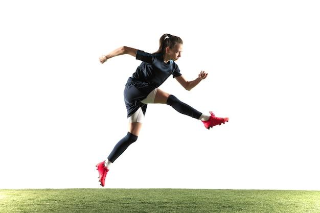 Młoda kobieta piłkarz lub piłkarz z długimi włosami w odzieży sportowej i butach, kopiąc piłkę do bramki w skoku na białym tle. pojęcie zdrowego stylu życia, sportu zawodowego, hobby.