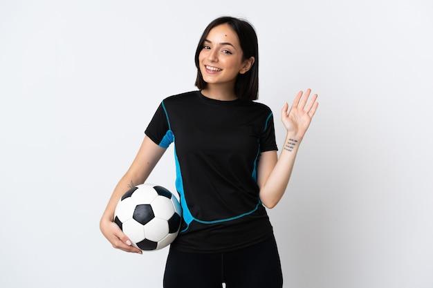 Młoda kobieta piłkarz na białym tle na białym tle salutowanie ręką z happy wypowiedzi