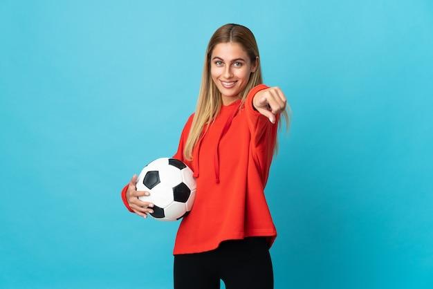Młoda kobieta piłkarz na białym tle na niebieskiej ścianie, wskazując przód z happy wypowiedzi