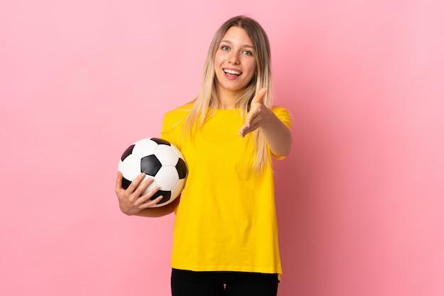 Młoda kobieta piłkarz na białym tle na różowy handshaking ściany po dobrej ofercie