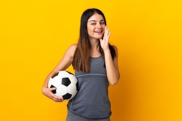 Młoda kobieta piłkarz na białym tle na żółtej ścianie krzycząc z szeroko otwartymi ustami