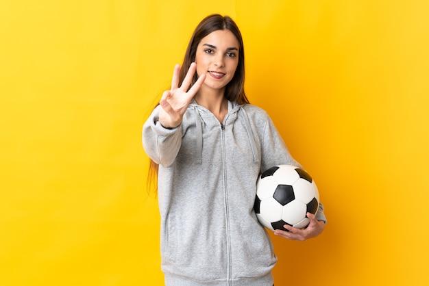 Młoda kobieta piłkarz na białym tle na żółtej ścianie szczęśliwa i licząc trzy palcami