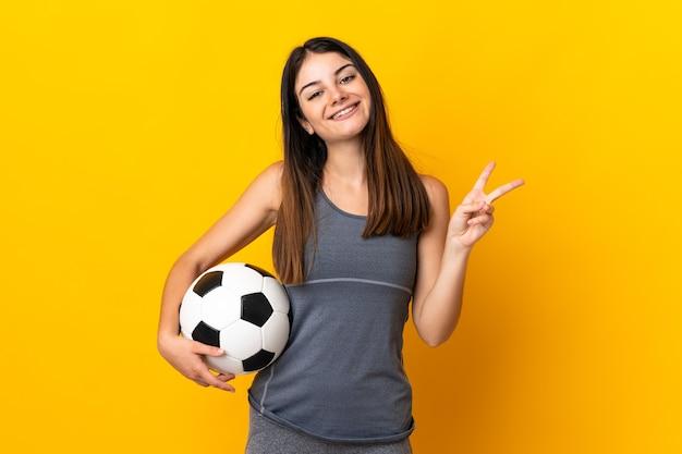 Młoda kobieta piłkarz na białym tle na żółty uśmiechnięty i pokazujący znak zwycięstwa