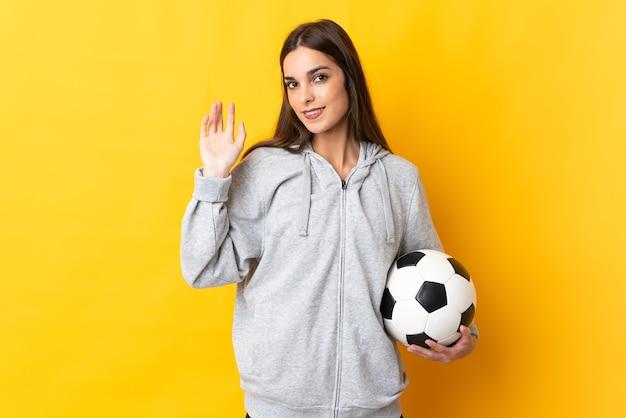 Młoda kobieta piłkarz na białym tle na żółtym tle salutowania ręką z happy wypowiedzi
