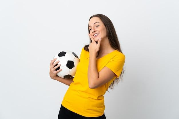 Młoda kobieta piłkarz na białym tle szczęśliwa i uśmiechnięta