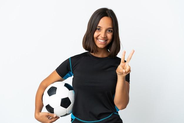 Młoda kobieta piłkarz na białym tle uśmiecha się i pokazuje znak zwycięstwa