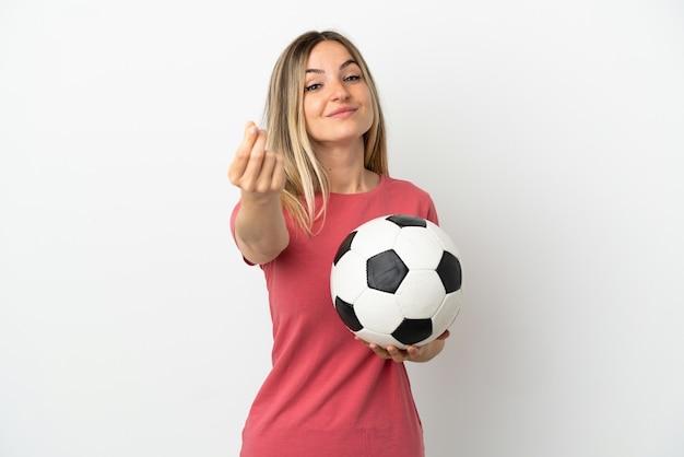 Młoda kobieta piłkarz nad odosobnioną białą ścianą gest zarabiania pieniędzy
