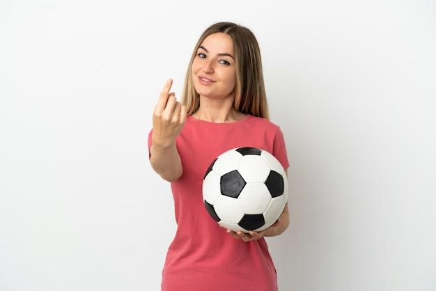 Młoda kobieta piłkarz nad odosobnioną białą ścianą robi nadchodzący gest